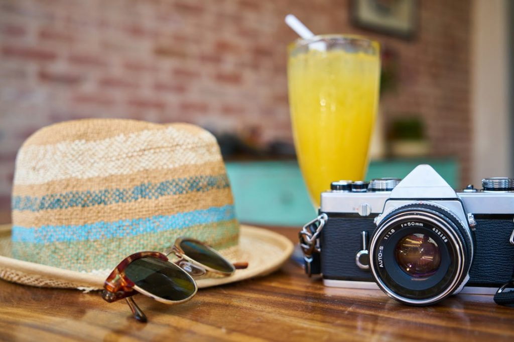 Sommerhut, Fotoapparat und Limonadenglas