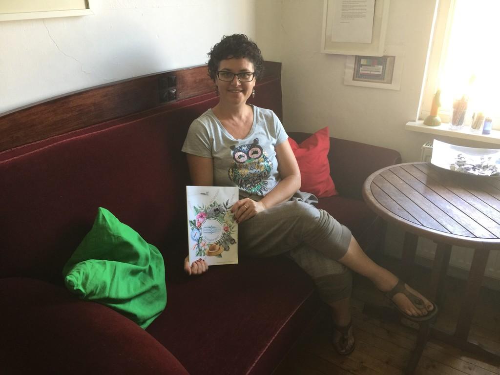 Sonia Lauinger mit Buch auf einem Sofa