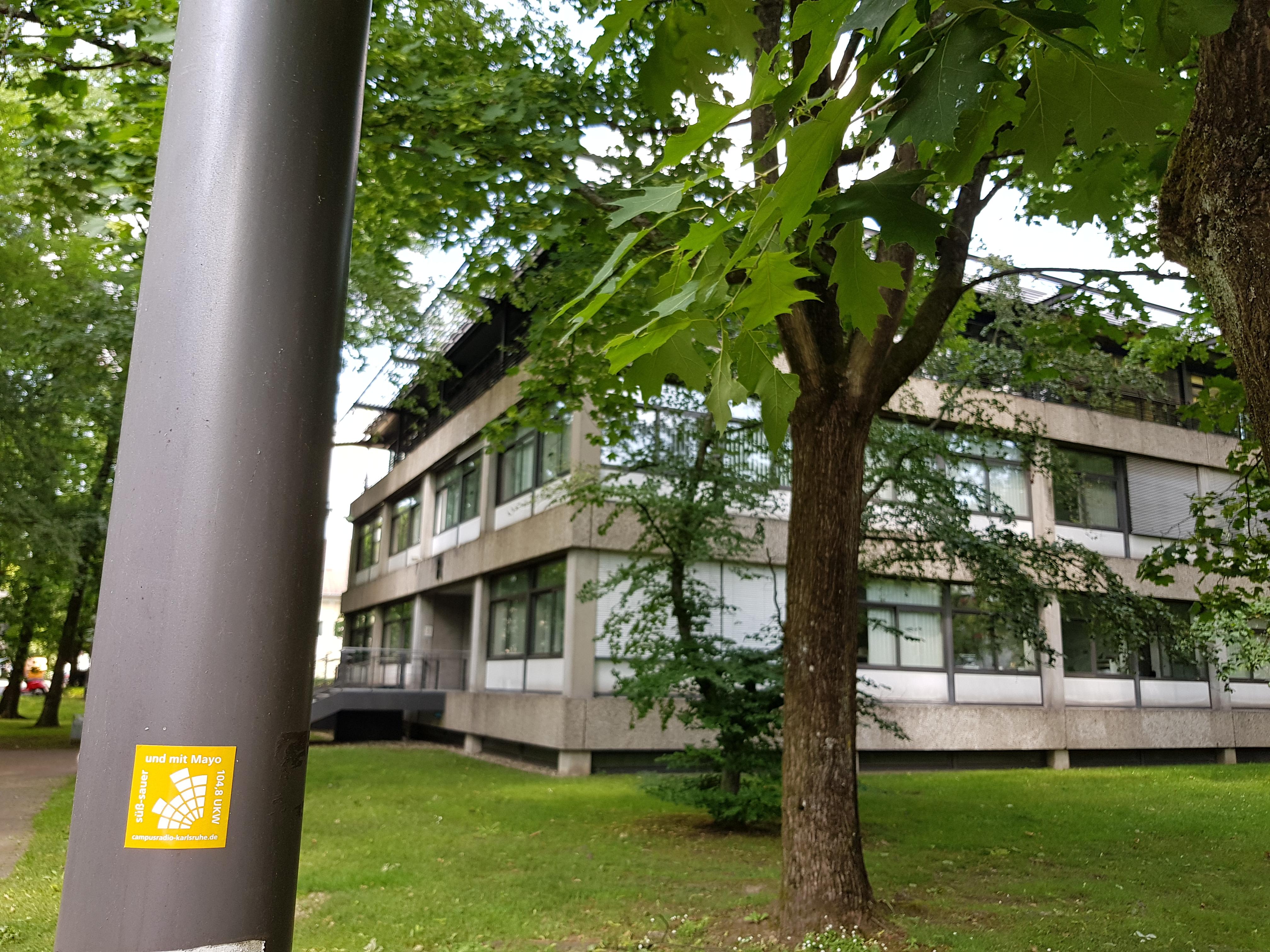 Laternenmast vor Hochschulgebäude mit Campusradio-Sticker