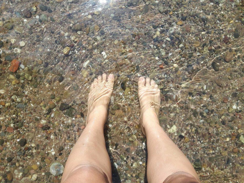 Ein paar Füße im klaren Flusswasser