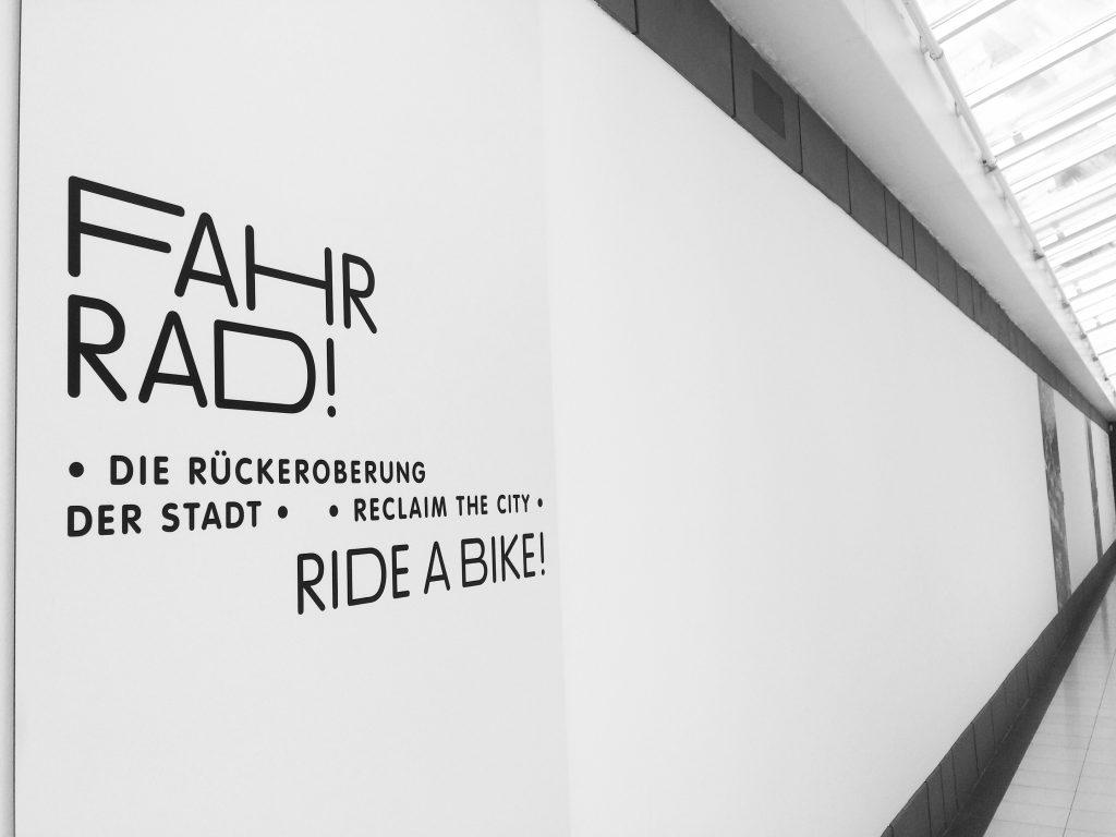 "Schriftzug an weißer Wand zur Ausstellung ""Fahr Rad!"""