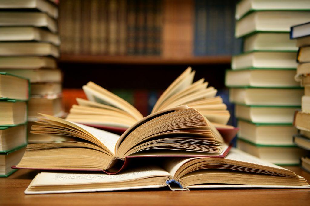 Bücherstapel und aufgeschlagene Bücher