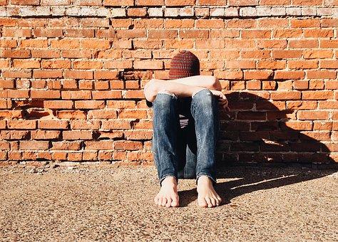 Junger Mann sitzt mit gesenktem Kopf auf dem Boden