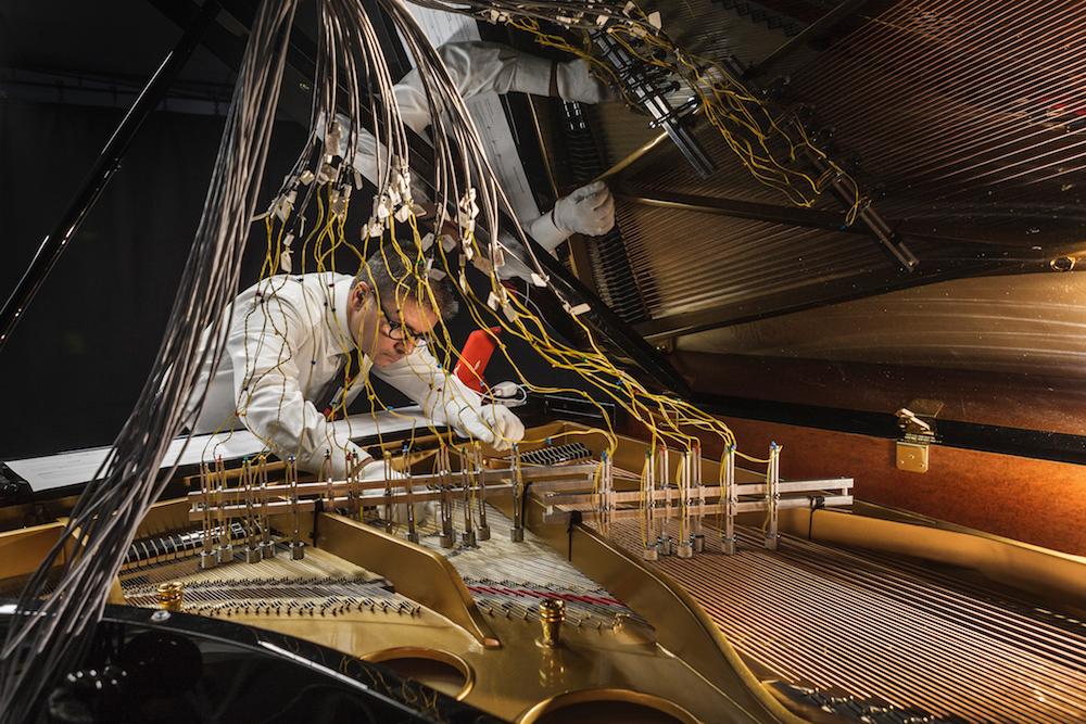 Mann über einem Klavierflügel, dessen Seiten mit Kabeln verbunden sind