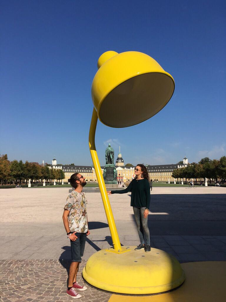 Josh und Francesca auf einer großen Schreibtischlampe als Kunstinstallation