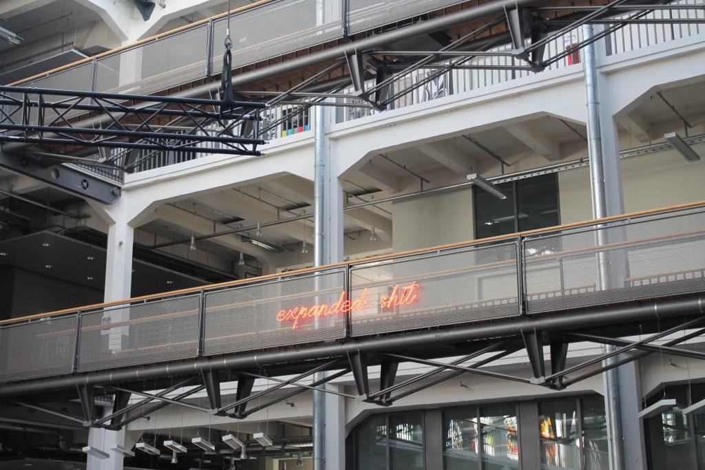 """Leuchtender Schriftzug """"expanded shit"""" an einem Galerie-Geländer"""
