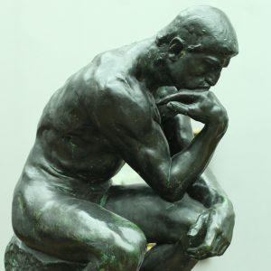 Statue eines sitzenden Mannes mit aufgestützem Kopf
