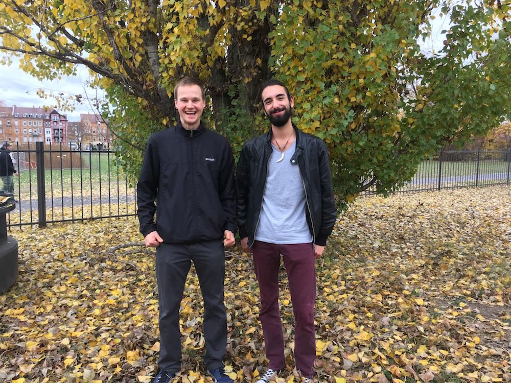 Moderatoren Josh und Steffen auf einer Wiese mit Herbstlaub