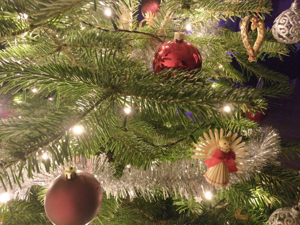 Tannenzweige mit Christbaumkugeln und Lichtern