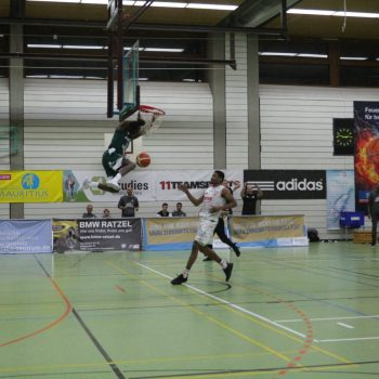 Spieler beim Basketballspiel springt an den Korb