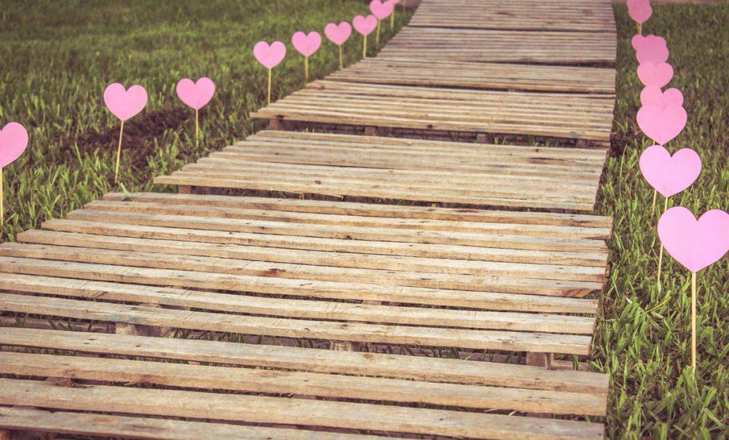 Ein Weg mit Holzplanken, rechts und links dekoriert mit Herzen.