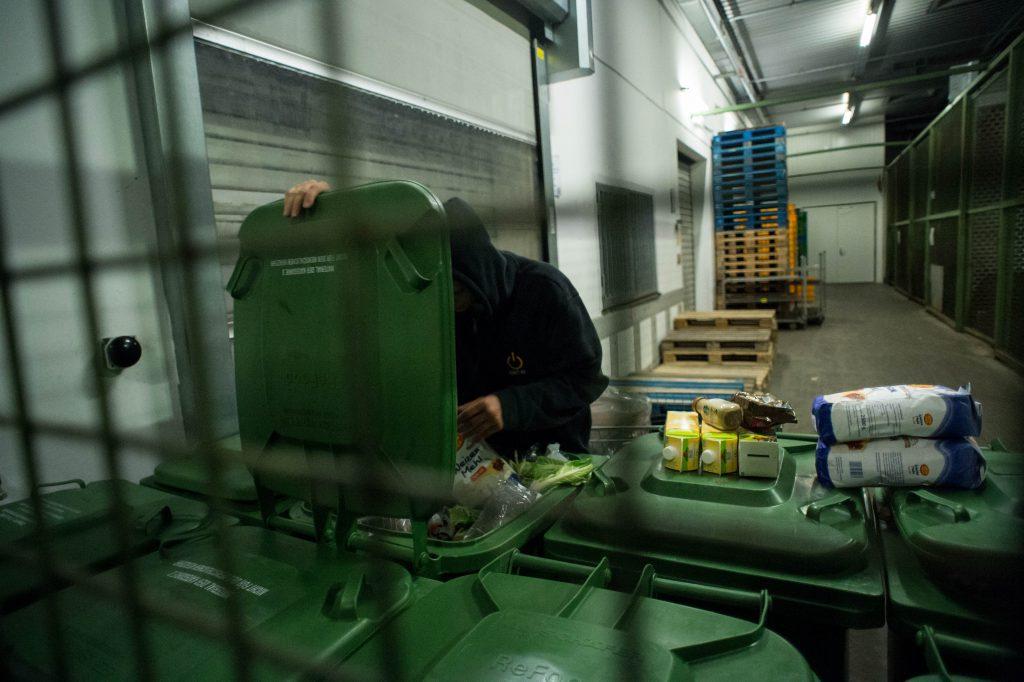 Junger Mann holt Lebensmittelpackungen aus einer großen Mülltonne