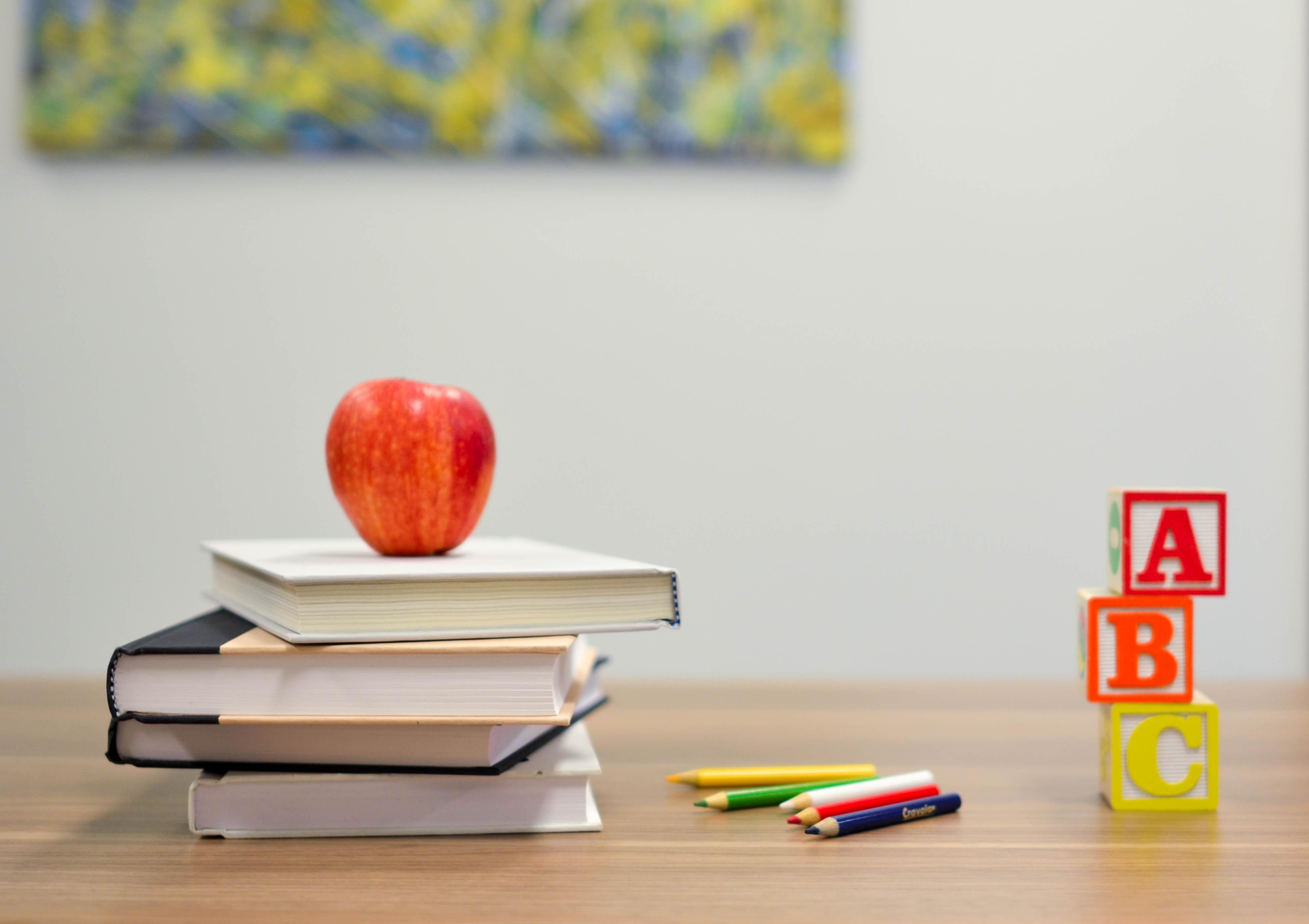 Tischplatte mit Bücher, Apfeö, Stiften und Bauklötzen