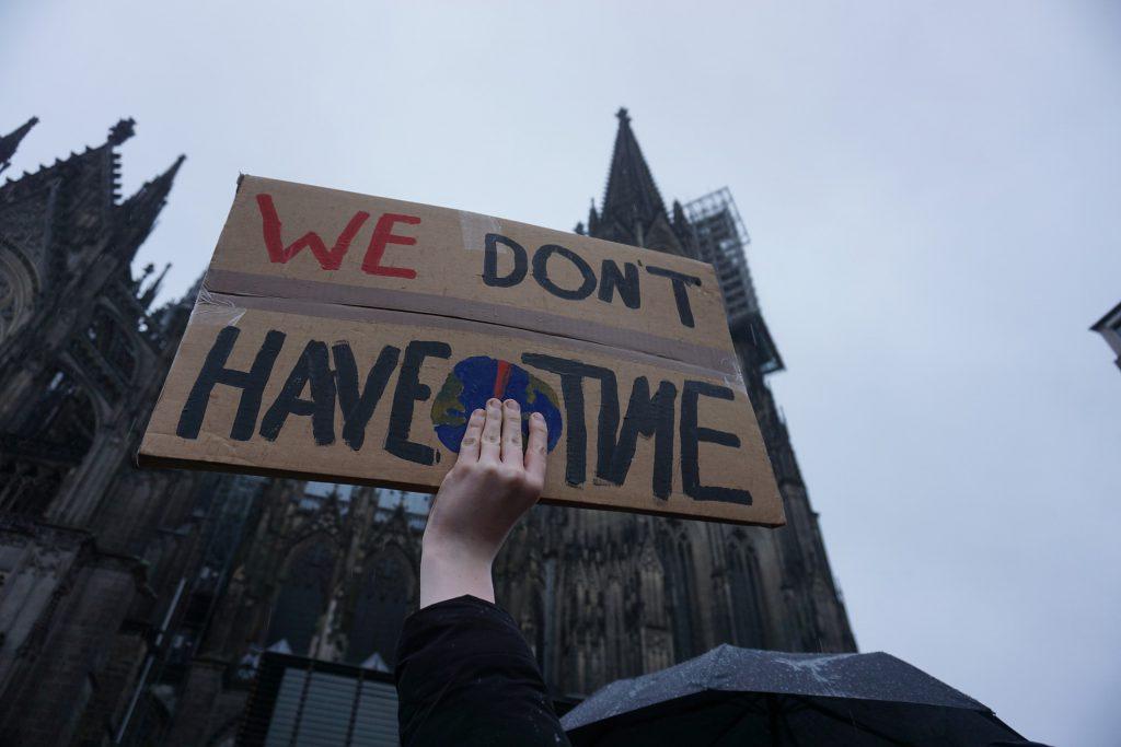 """Aktivist hält Pappschild vor Kölner Dom hoch mit Aufschrift """"We don't have time"""""""