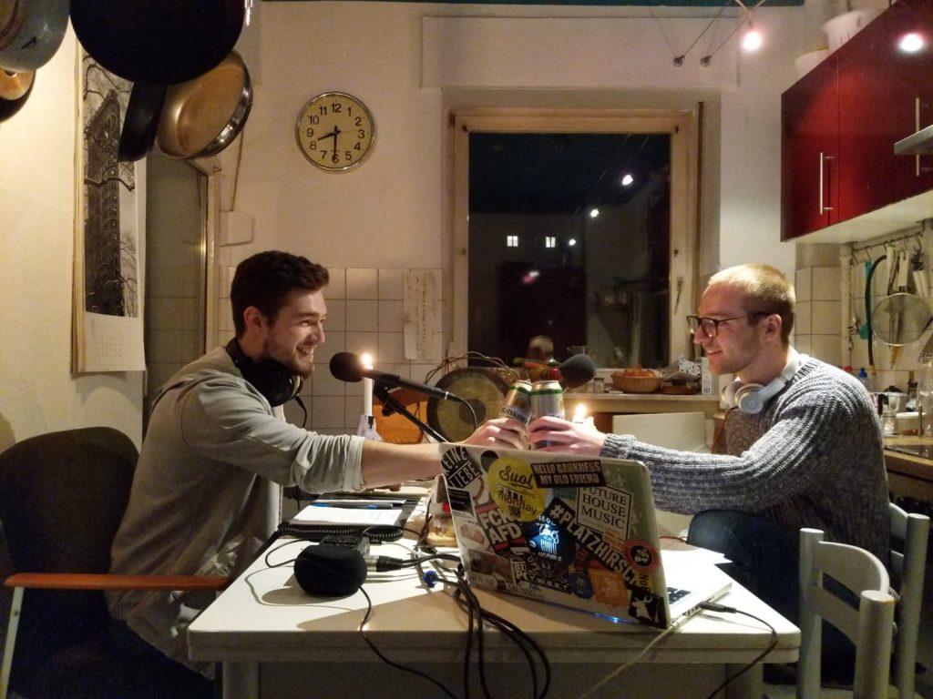 Moderatoren Yannick und Chris sitzen in einer Küche am Tisch