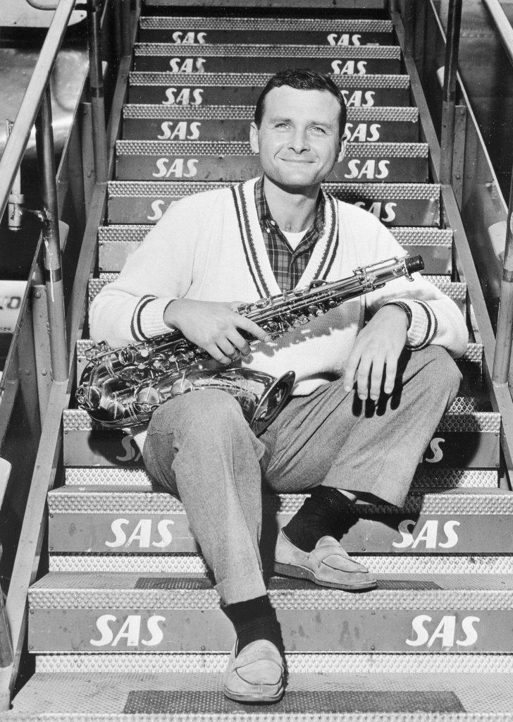 Mann sitzt auf einer Treppe und hält ein Saxophon