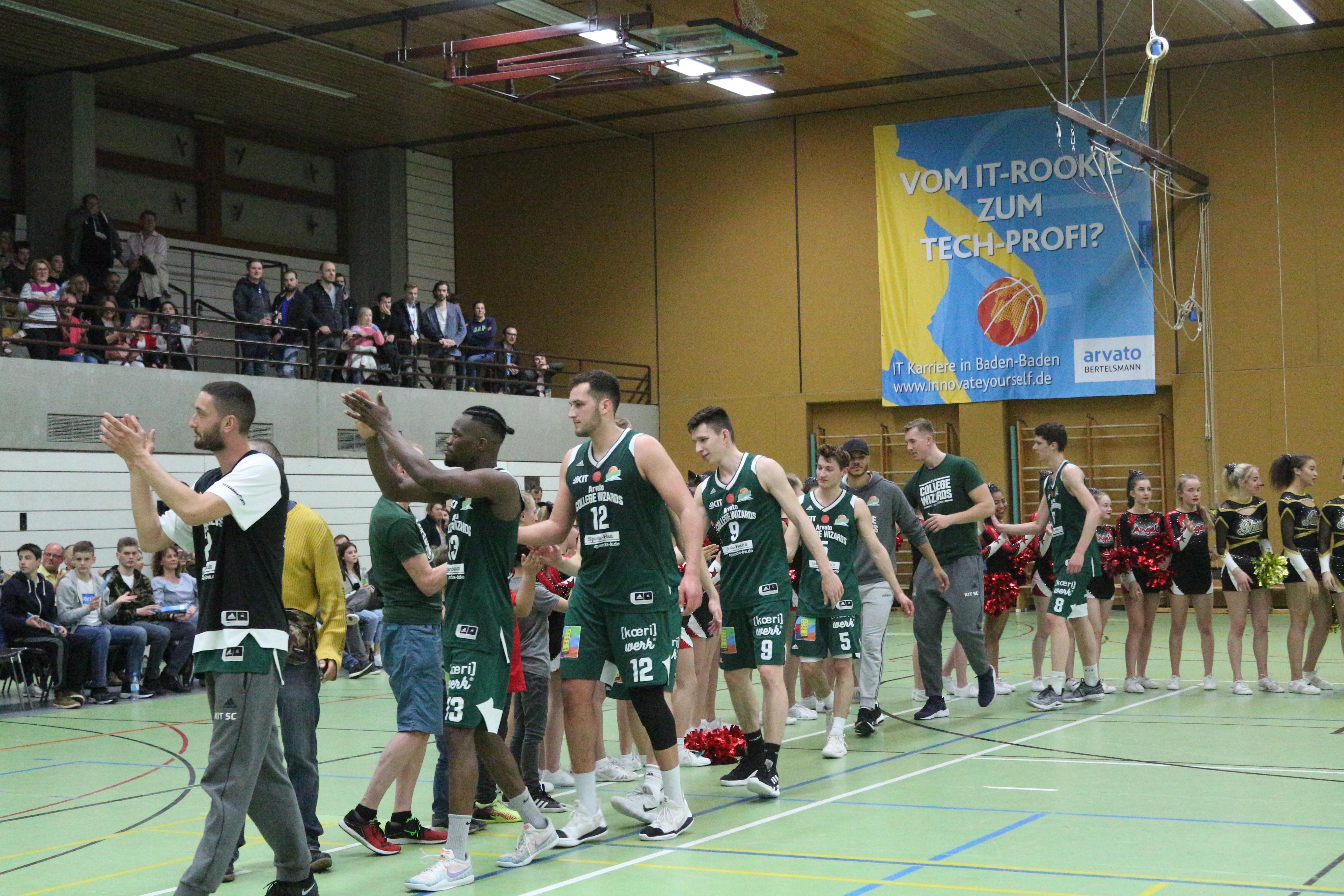 KIT-Basketballteam läuft aus der Halle und winkt ins Publikum