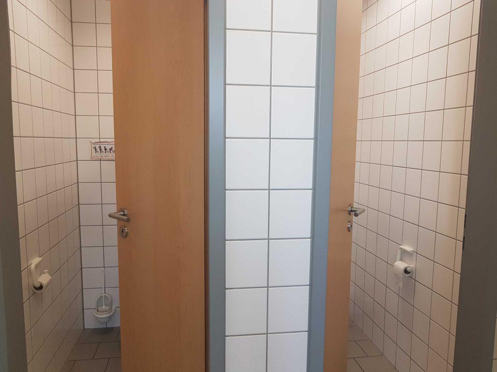 Blick auf zwei geöffnete Toilettentüren