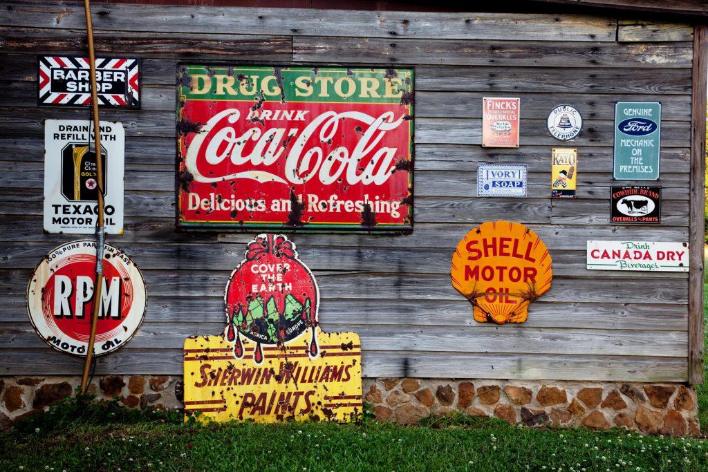 Werbe-Blechschilder an einer Holzwand