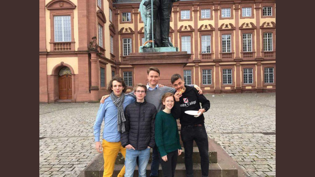 Fünf junge Erwachsene vor einer Schlosskulisse