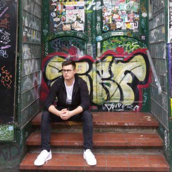 junger Mann sitzt auf einer Treppe vor einer Tür mit Graffiti