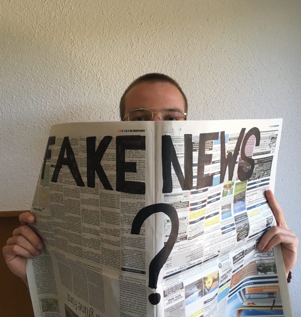 "Mann hält Zeitung mit Aufschrift ""Fake News?"""