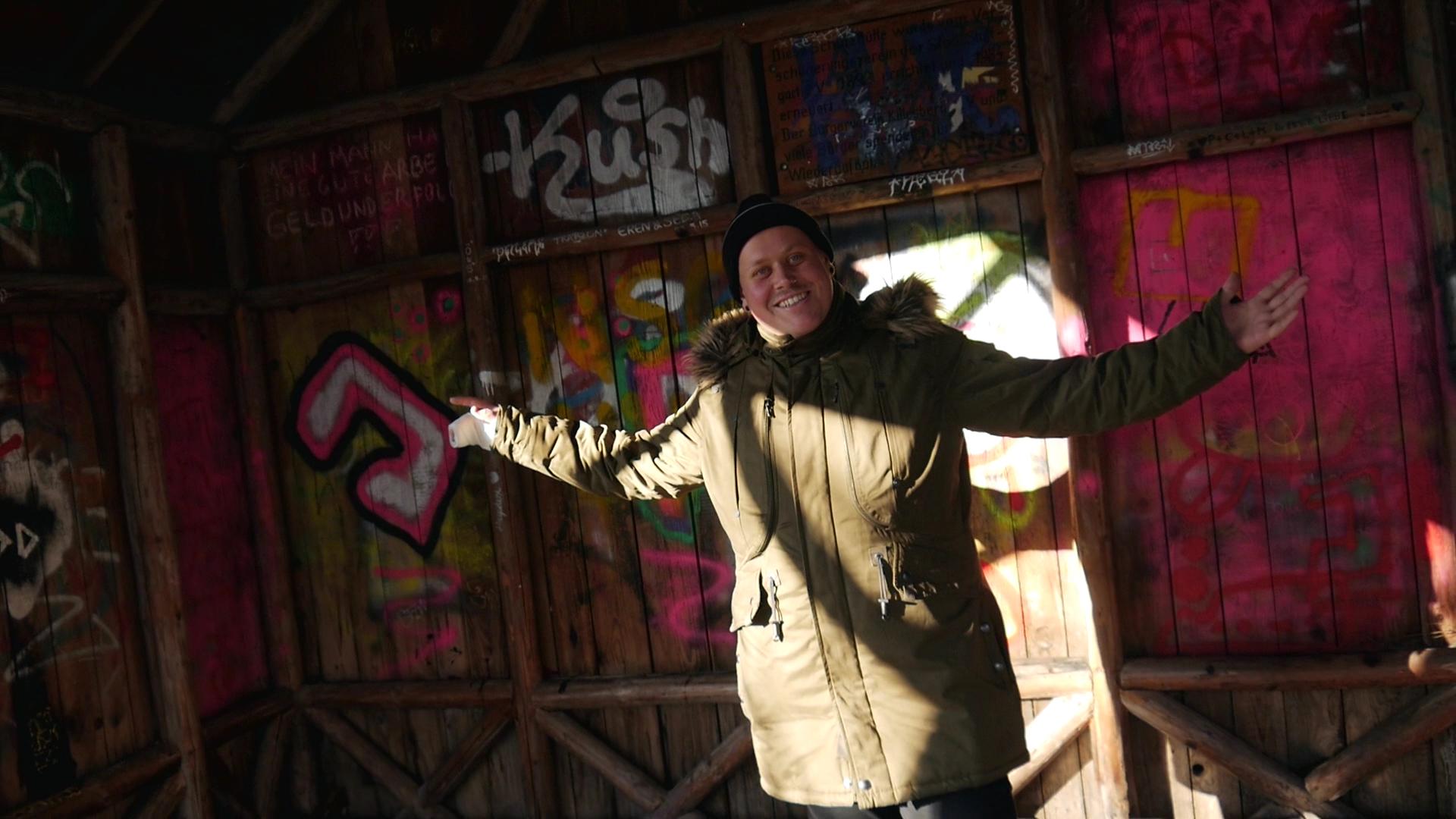Mann steht mit ausgestreckten Armen vor Wand mit Graffiti