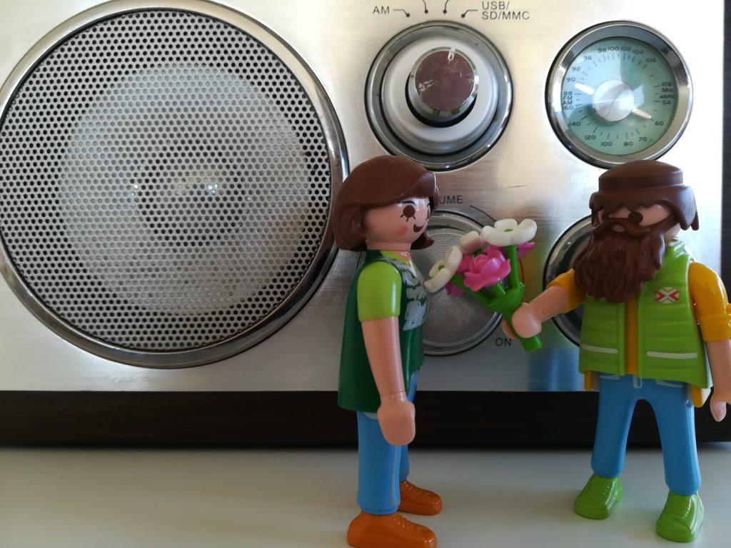 Zwei Playmobilfiguren mit einem Blumenstrauß vor einem Radiogerät
