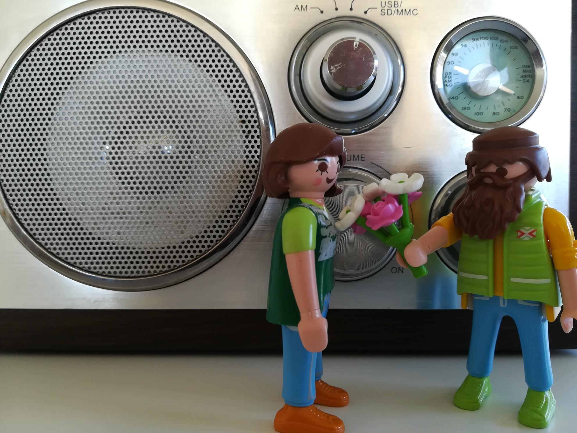 Zwei Playmobilfiguren mit Blumenstrauß vor einem Radiogerät