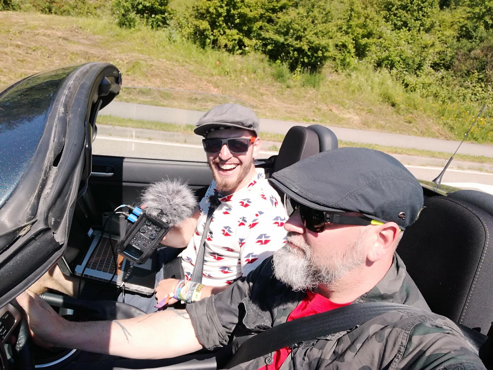 Zwei Männer im fahrenden Cabrio mit Tonaufnahmegerät