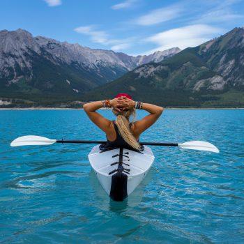 Frau im Kajak auf einem See mit Blick auf Berge