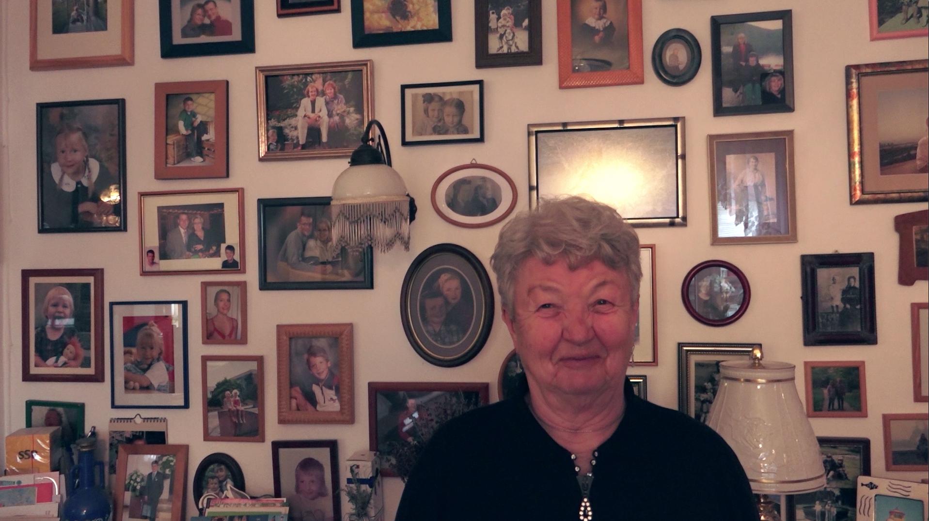 Seniorin vor Wand mit gerahmten Fotos
