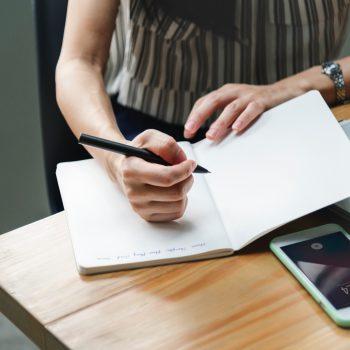 Frau mit Notizbuch am Laptop