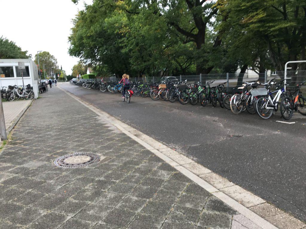 Straße, daneben ein Bürgersteig, auf dem viele Fahrräder geparkt sind
