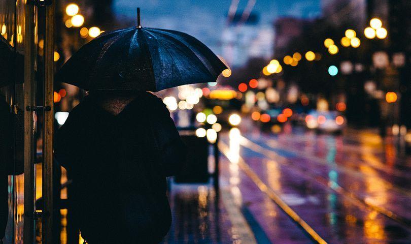 Schatten einer Person mit Regenschirm auf einer regennassen Straße