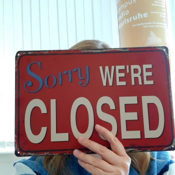 "Frau hält Schild hoch ""Sorry, we are closed"""