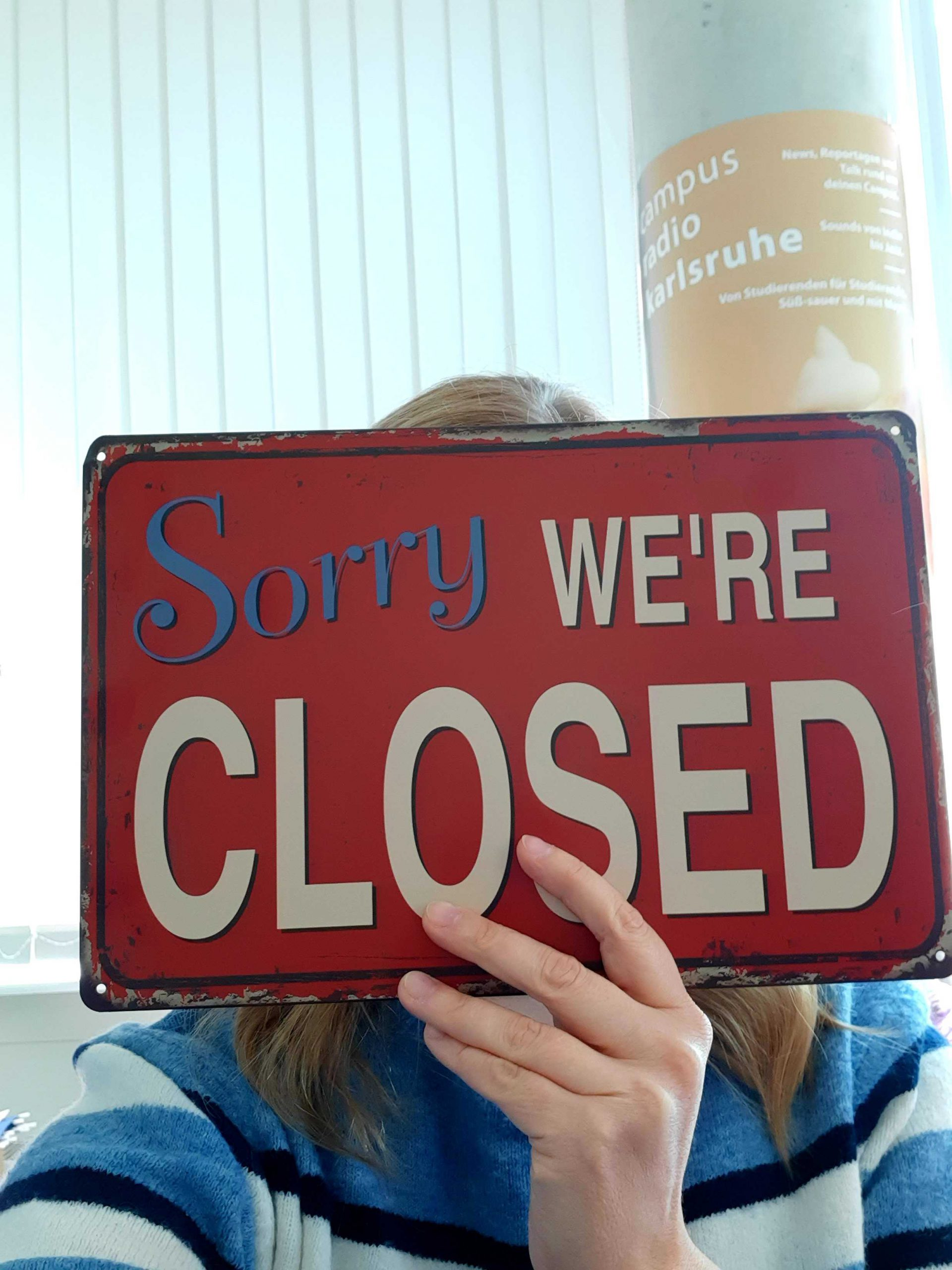 "Frau hält Schild hoch ""Sorry, we are closed"""