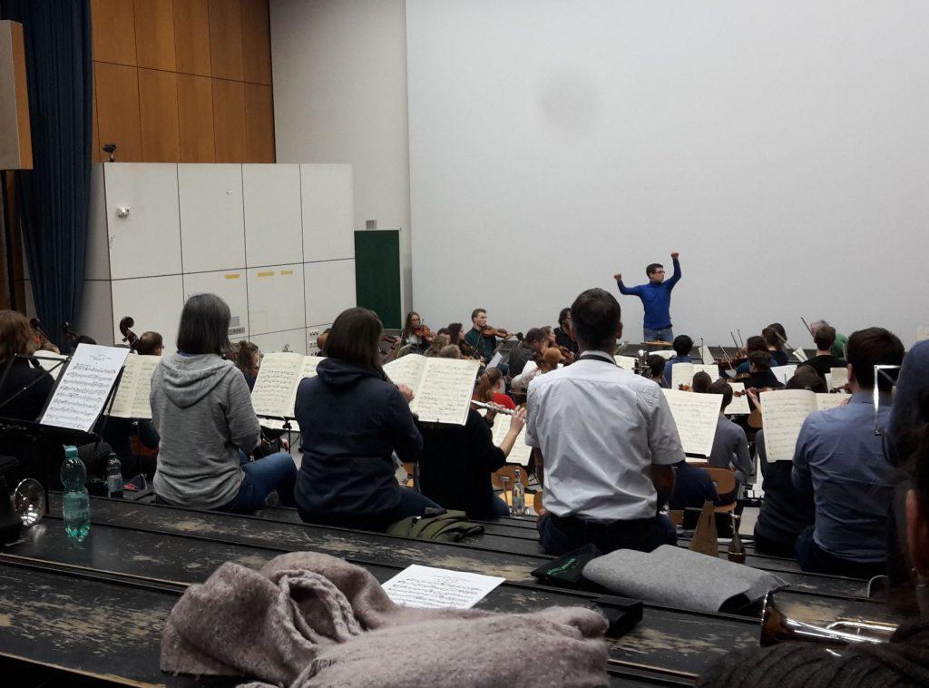 Orchester mit Dirigent bei Probe in einem Hörsaal