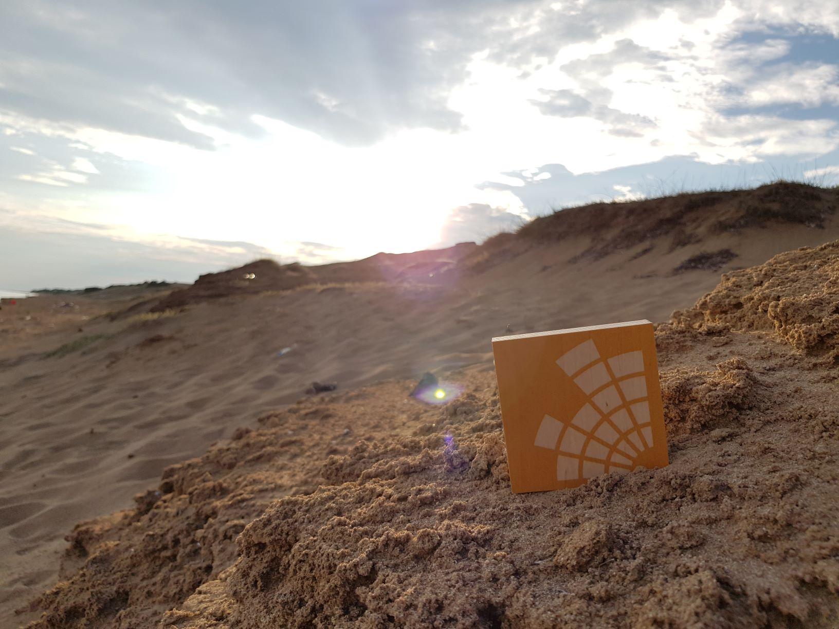 Holztafel mit Campusradio-Logo steckt in einem Berg von Sand