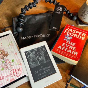 Tisch mit Büchern, E-Book-Reader und Kaffeetasse