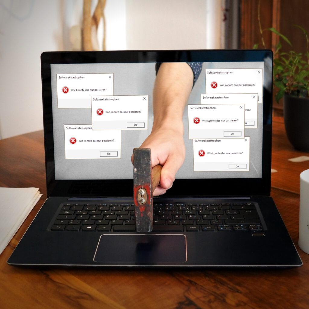 Laptop, aus dessen Bildschirm eine Hand mit Hammer ragt, die auf die Tastatur haut