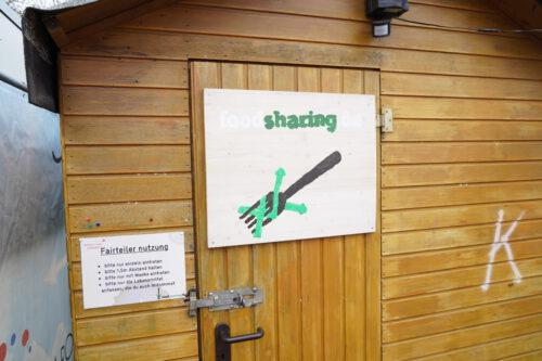 """Holzhütte mit Schild """"Fairteiler"""" an der Tür"""